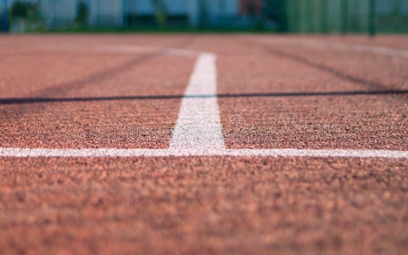 Basketballplatz-im Freien Three-Point- Linie Weiß auf Rot Schatten vom Fechten, unscharfer grüner Hintergrund lizenzfreies stockfoto