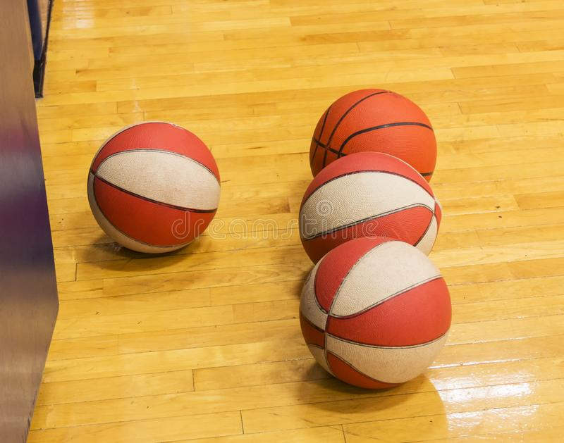 Basketballs on gym floor. Four basketballs isolated on a gym floor during baketball practice at a local high school royalty free stock images
