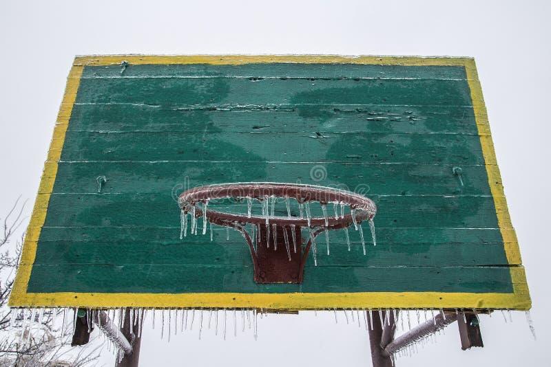 Basketbalrugplank en ring in de winter Met de hangende ijskegels van een basketbalhoepel Ijs Vorst Geen sporten Geen spelen stock foto