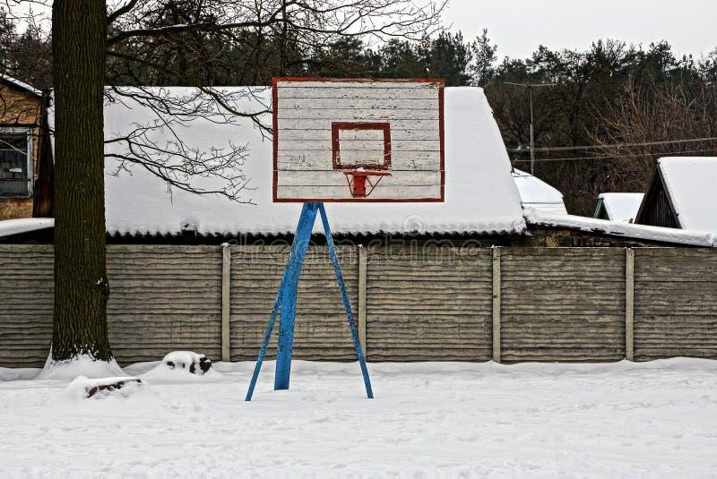 Basketbalschild op een lege sportengrond onder de sneeuw stock foto's