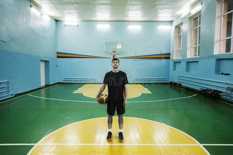 Basketbalspeler in actie in een basketbalhof stock afbeelding