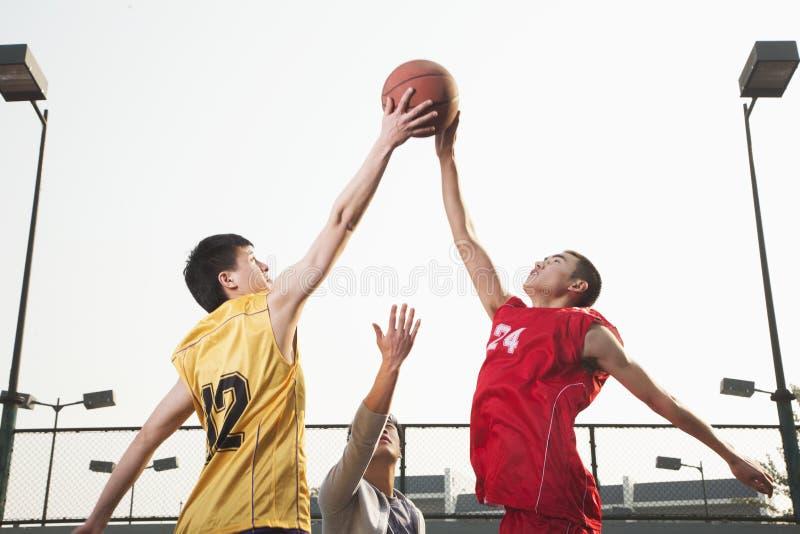 Basketbalspelers die voor een bal vechten stock afbeelding