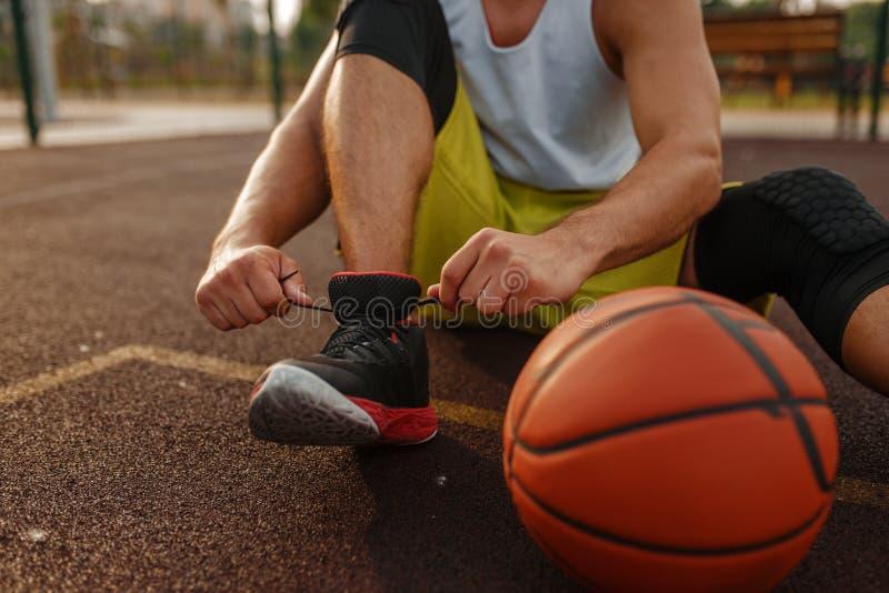 Basketbollspelare som binder laces på utomhusdomstolar arkivfoton