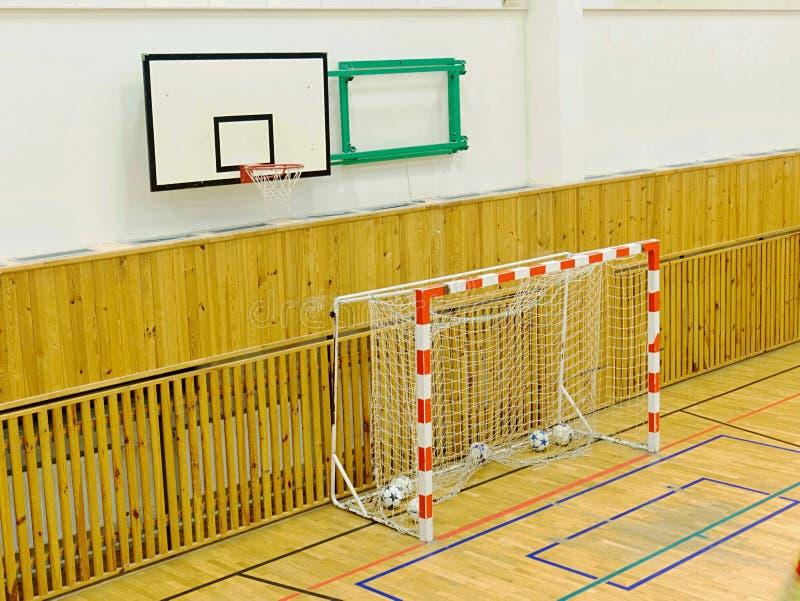 Basketbräde och futsal port i skolaidrottshall Centralvärme arkivbild
