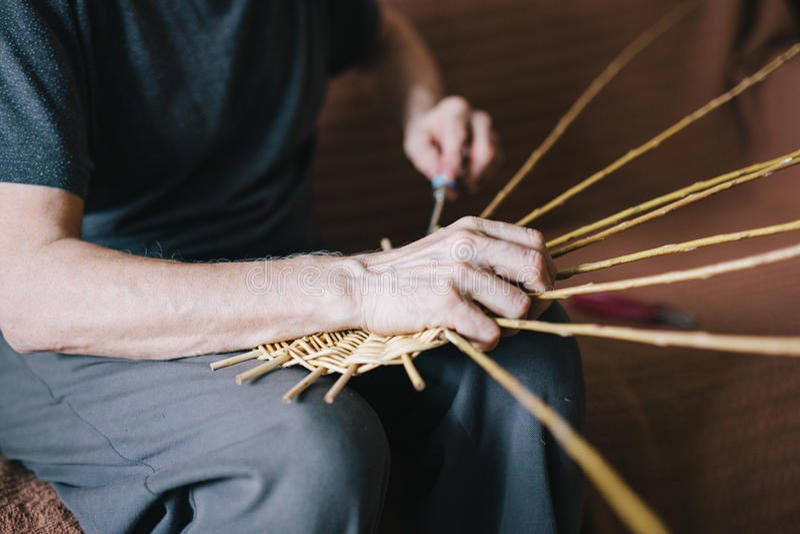 Basketry. Man`s hands making a wicker basket stock photo