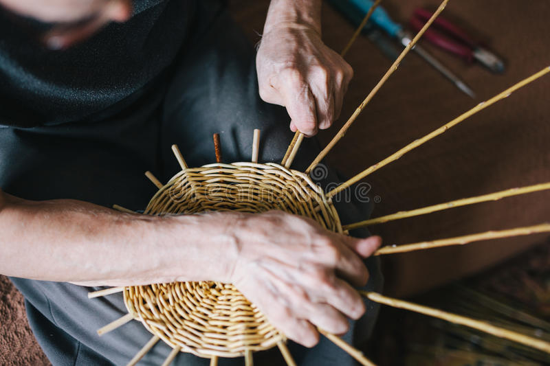 Basketry. Man`s hands making a wicker basket royalty free stock images