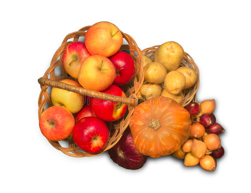 Baskets filled with ripe apples, onions, potatoes and pumpkin stock images