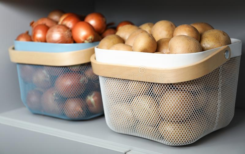 Baskets with potatoes and onions on shelf royalty free stock photography