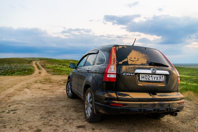 BASKUNCHAK, РОССИЯ - 28-ОЕ МАЯ 2019: Пылевоздушный кроссовер Honda CRV SUV на сельской дороге в степи стоковые изображения