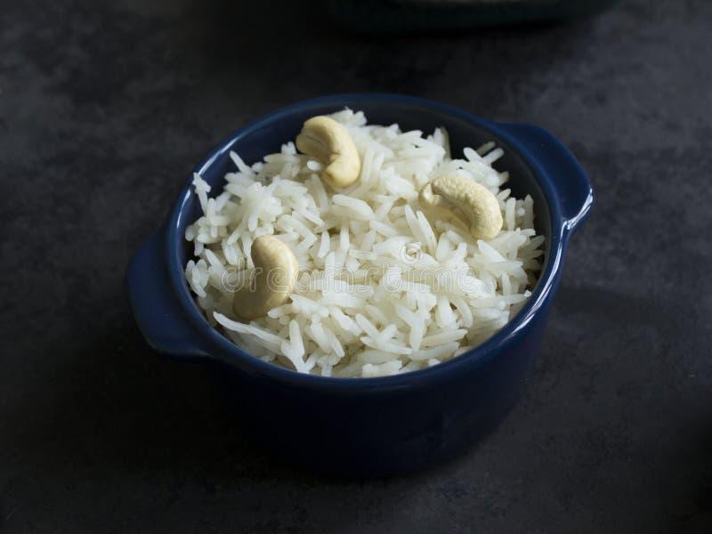 Basmati gekookte rijst met cashewnoten in een donkerblauwe pot op een donker oppervlak royalty-vrije stock afbeeldingen