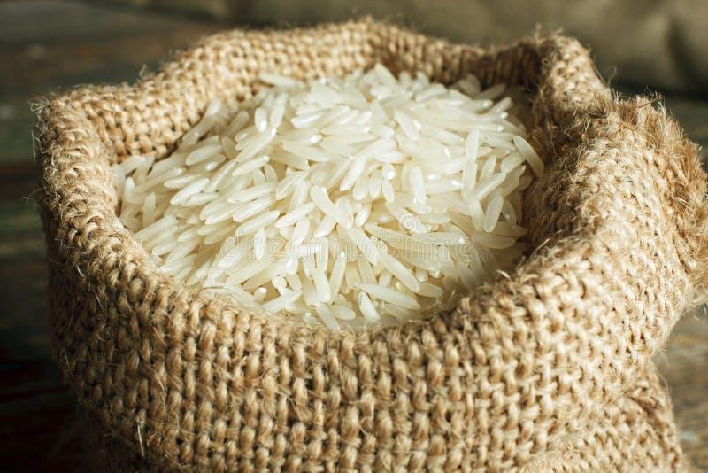 Basmati rice. White uncooked basmati rice in burlap bag stock photography