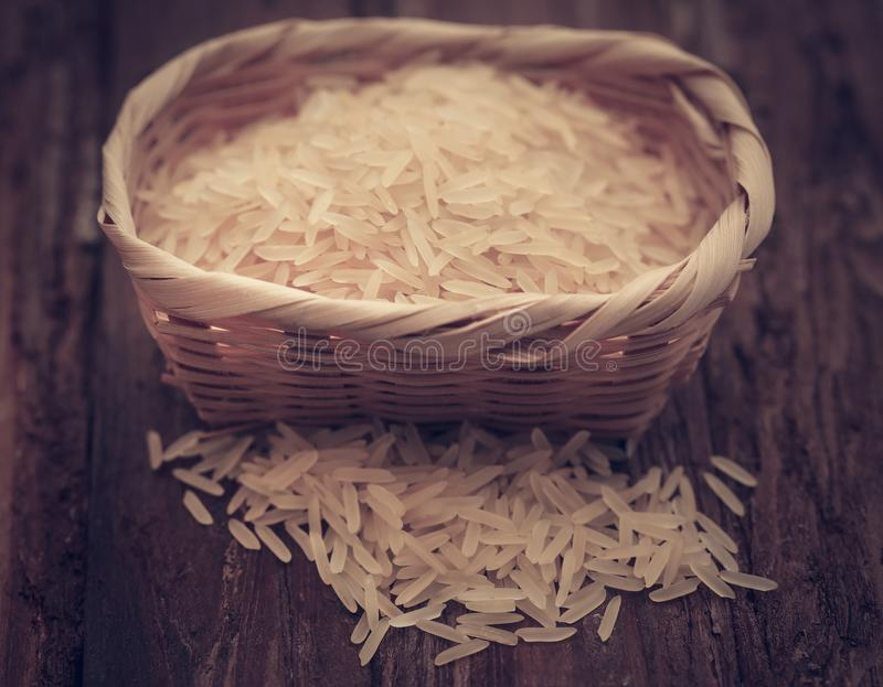 Basmati rice. In a basket on wooden surface royalty free stock image