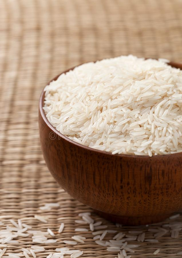 Basmati rice. In wooden bowl on straw background royalty free stock photography