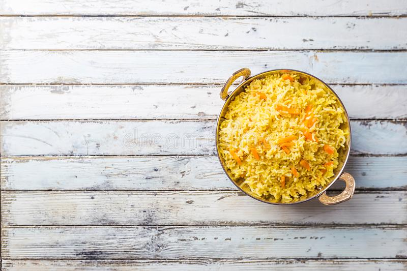 Basmati rice with curry. Fried in stainless copper pan over white wooden background, top view stock image