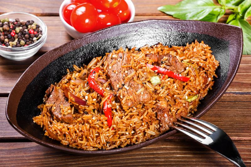 Basmati rice with meat, vegetables and aromatic spices on wooden table royalty free stock photo