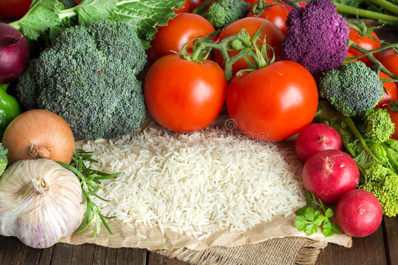 Basmati rice and vegetables. Pile of Basmati rice and vegetables on wood royalty free stock photos