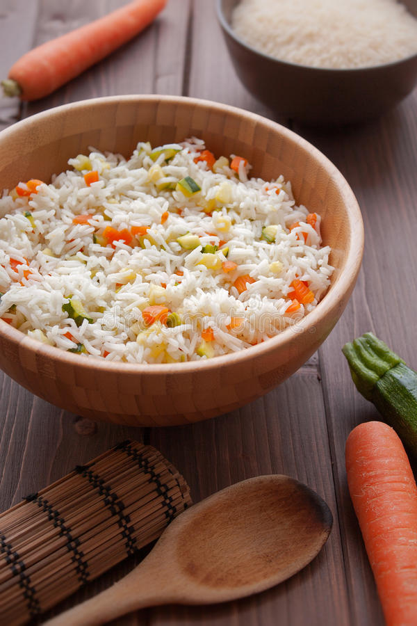 Basmati Rice with veggies. Basmati rice with carrots and courgettes in a dish on wood table stock image