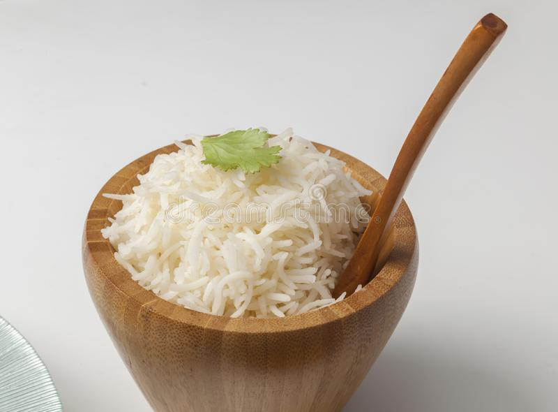 Basmati rice served in bowl. Basmati rice in a wooden bowl with spoon stock images