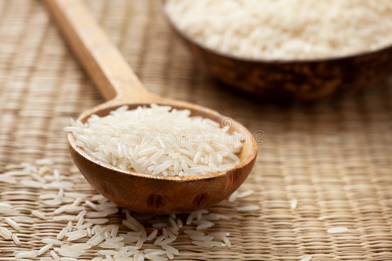 Basmati rice. In wooden spoon on straw background royalty free stock photography