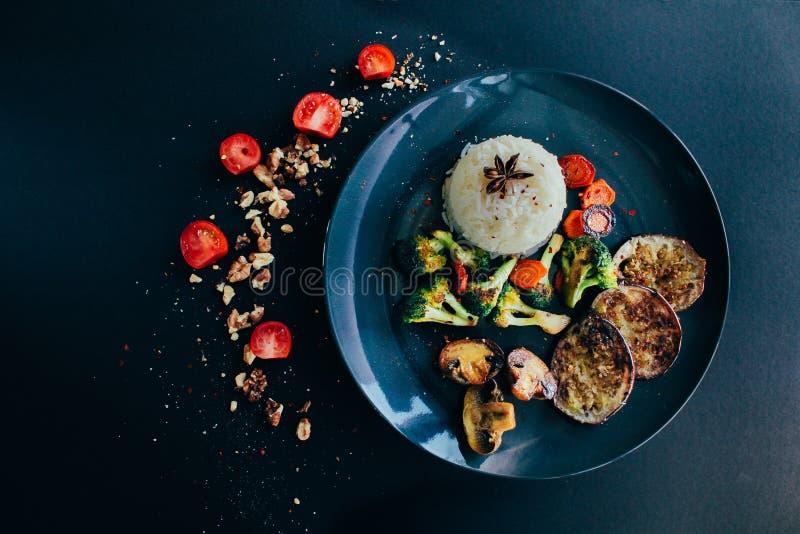 Basmati rijst, vegetariër, veganist geroosterde groenten Wortel, kersentomaten, champignons, aubergine, anijsplant donker stock afbeeldingen