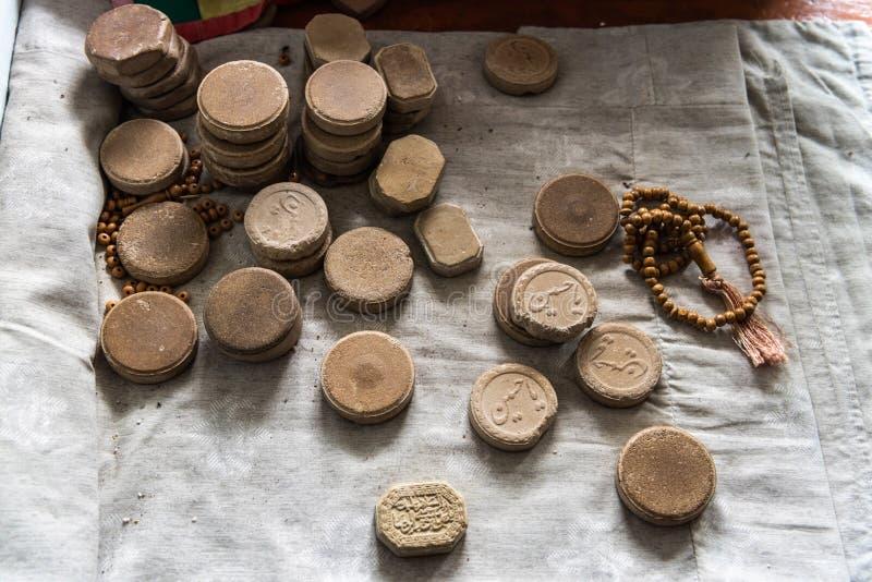 Clay turbah tablets with prayer beads. Basqal, Ismayilli region, Azerbaijan - April 30, 2019. Clay turbah tablets with prayer beads. Turbah is a small piece of stock photos