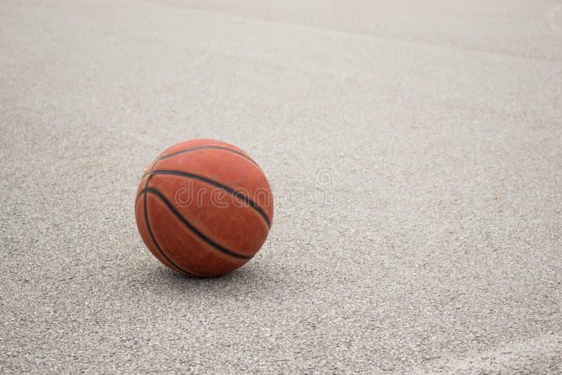 Basquetebol de couro alaranjado usado no fundo cinzento do asfalto fotos de stock royalty free