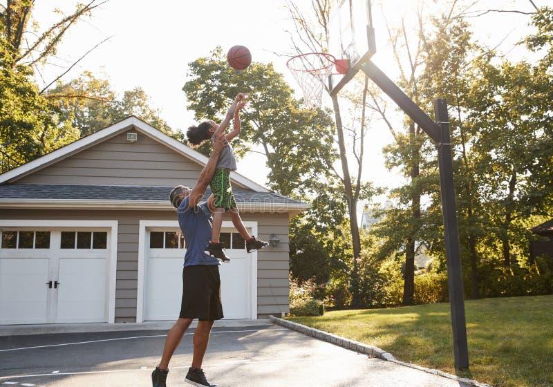 Basquetebol de And Son Playing do pai na entrada de automóveis em casa foto de stock