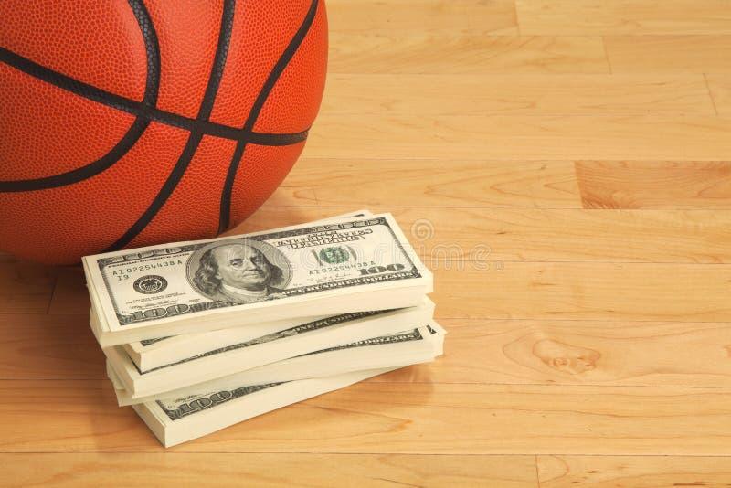 Basquetebol e cem notas de dólar no assoalho de madeira da corte foto de stock