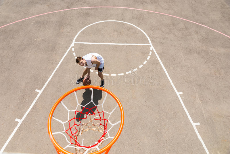Basquetebol pingando do homem novo abaixo da rede na corte foto de stock royalty free