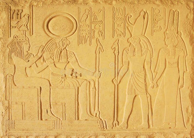 Basrelief för sandfärgmurbruk med gudarna av forntida Egypten, ROMMARNA för solgud, guden Horus och de två gudinnorna arkivbilder