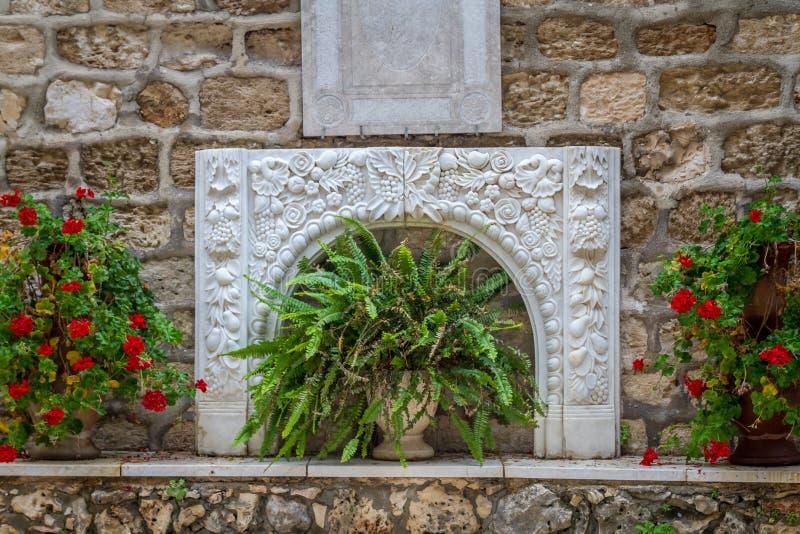 Basrelief och blommor, borggård av den grekiska ortodoxa bröllopkyrkan i Cana, Israel royaltyfri fotografi