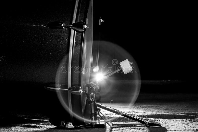 The bass drum pedal in low light background, balck and white. The bass drum pedal in low light background, balck and white, flare light royalty free stock photo