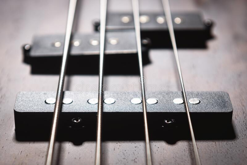Bass electric guitar with four strings closeup. Detail of popular rock musical instrument. Close view of element of wooden royalty free stock photos