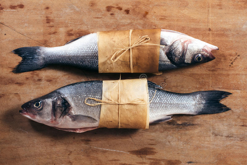 Bass fish. Couple of raw bass fish on the wooden background stock image