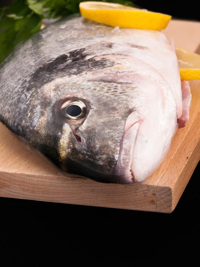 Bass fish with slices of lemon. Bass fish with lemon on a wooden table royalty free stock photos