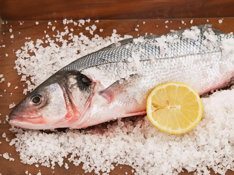 Bass fish with salt and lemon. On a wooden table royalty free stock photos