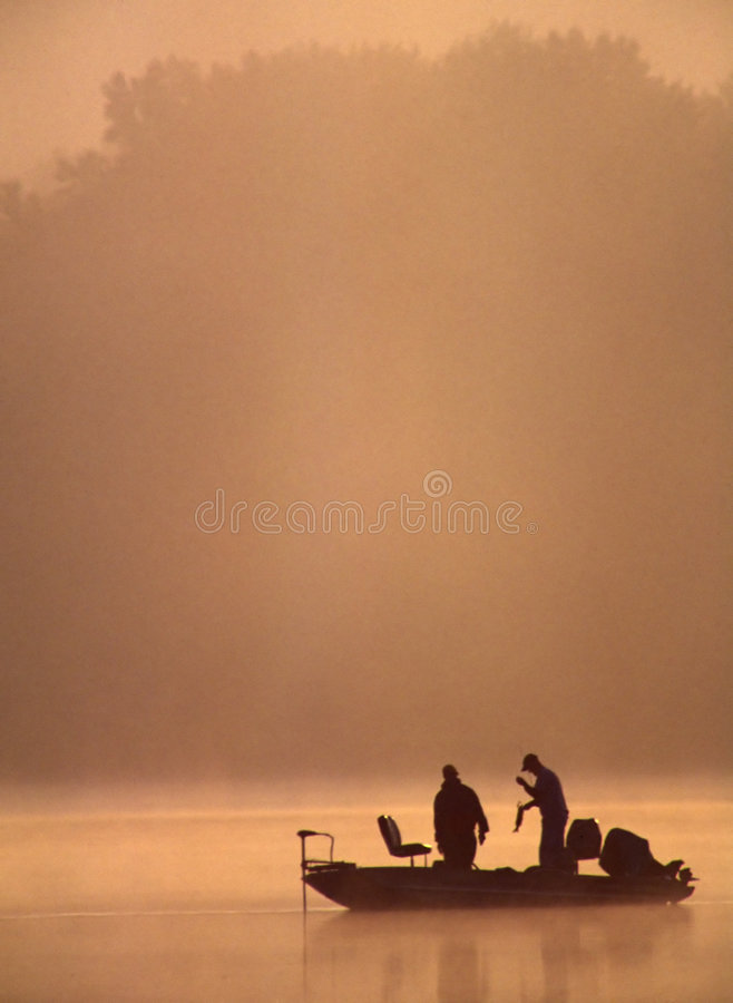 Bass Fishermen Admiring Their Catch. A couple of fishermen are admiring the Large Mouth Bass they just caught on a beautiful misty morning stock photos