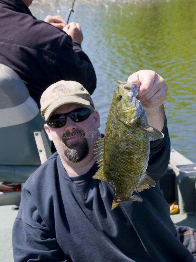 Bass Fishing. A fisherman with a Small Mouth Bass on a Minnesota Lake stock image