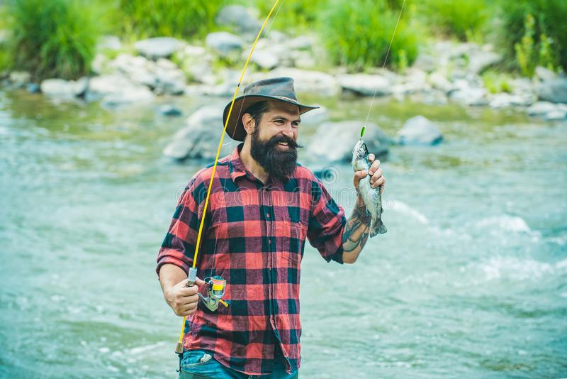 Bass fishing. Fisherman and trophy trout. River grayling on the hook. sport fishing. Method for catching trout. Fishing royalty free stock photo