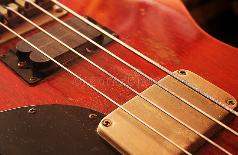 Bass guitar. Red worn out bass guitar royalty free stock image