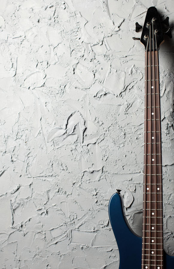 Bass guitar. Stands near the gray wall royalty free stock images