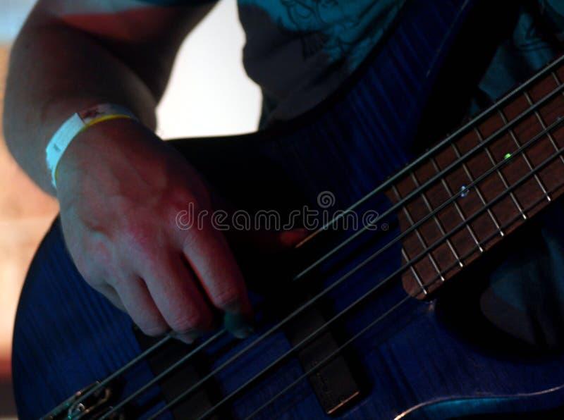 Bass Guitar Being Played azul imagem de stock