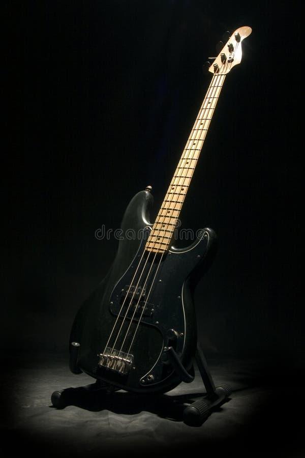 Bass guitar in dark. Bass guitar royalty free stock photography