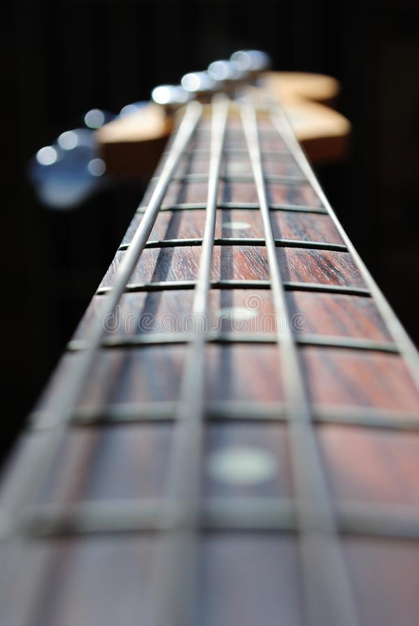 Bass Guitar Neck. Abstract view of a bass guitar neck isolated on black with a shallow depth of field, focus on the middle fret stock photos