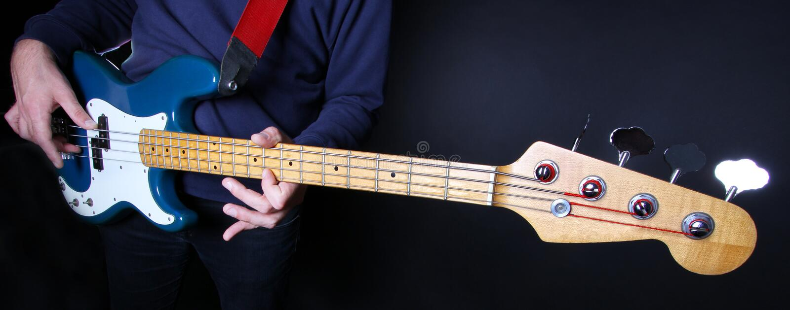 Bass guitar player. Man playing bass guitar on black background royalty free stock images