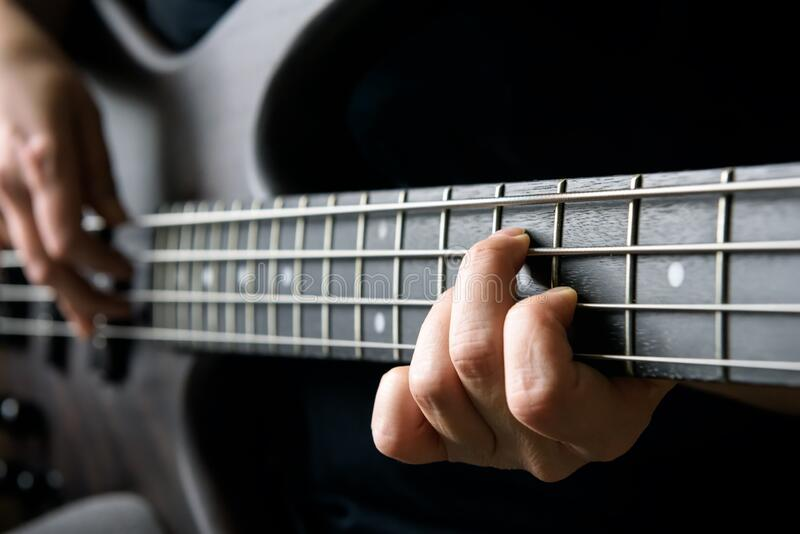 Bass guitar player hand closeup, lesson and practice theme. Playing on bass electric guitar, live music and skill concept. Close view of guitarist fingers on royalty free stock photo