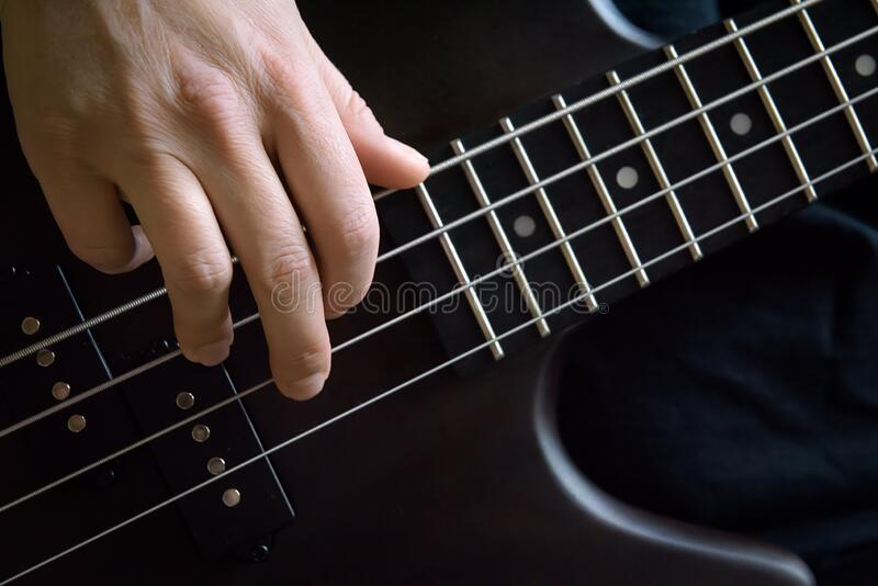 Bass guitar player hand closeup, lesson and practice theme. Playing on bass electric guitar, live music and skill concept. Close view of guitarist fingers and royalty free stock photography