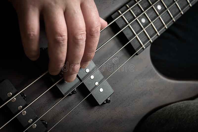 Bass guitar player hand closeup, lesson and practice theme. Playing rock on bass electric guitar, live music and skill concept. Close view of guitarist fingers royalty free stock photos