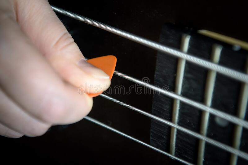 Bass guitar player with pick in his hand closeup, lesson and practice theme. Playing on bass electric guitar, live music and skill. Bass guitar player with pick stock image