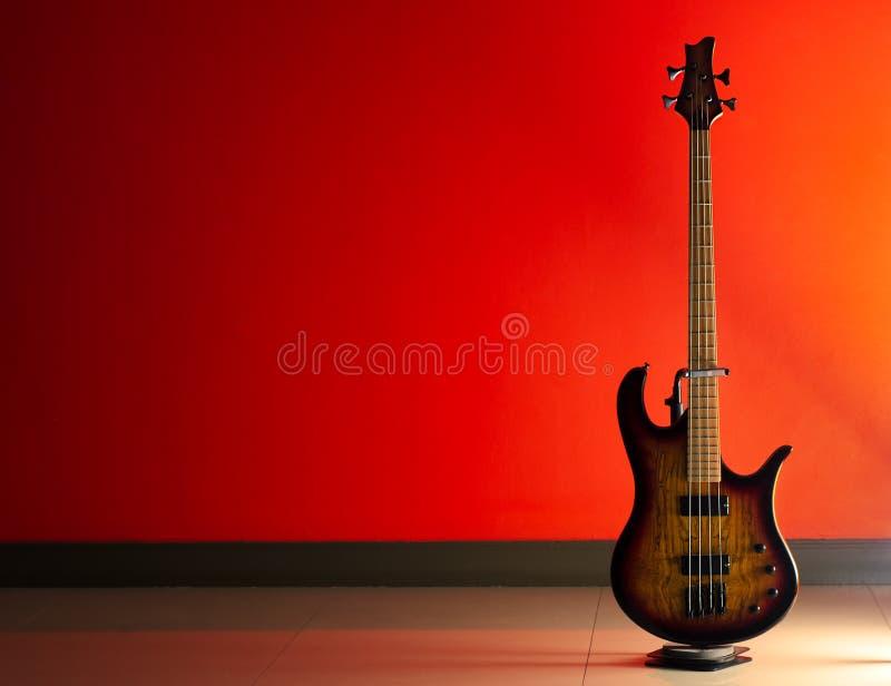 Bass Guitar sur un fond rouge images stock
